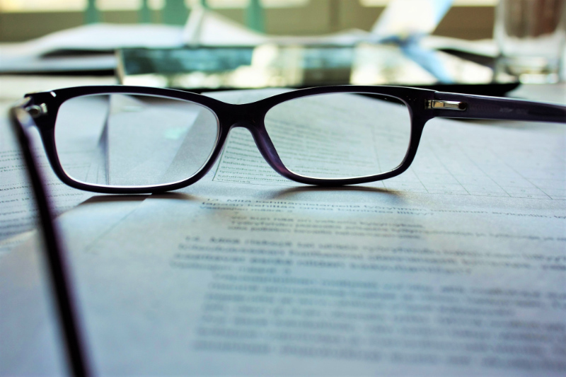 A pair of black glasses sitting on a report