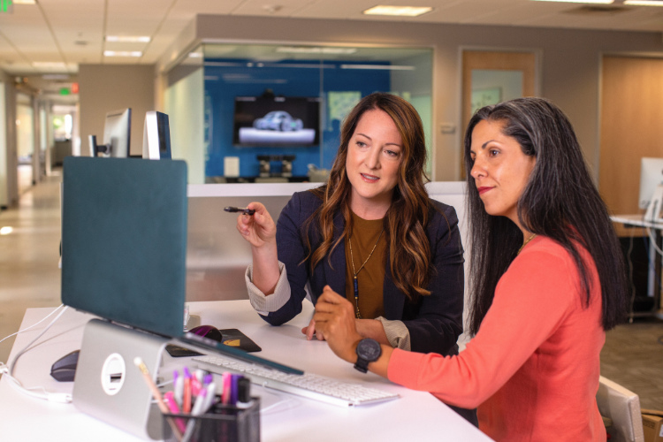 Two female co-workers looking at a laptop screen