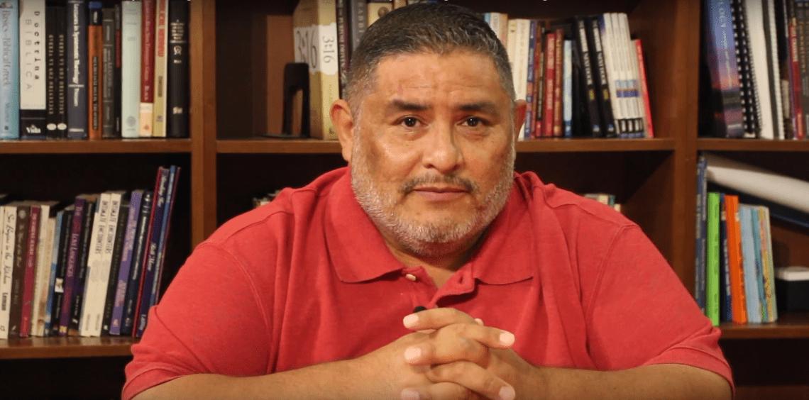 Pastor Luis in front of a bookshelf