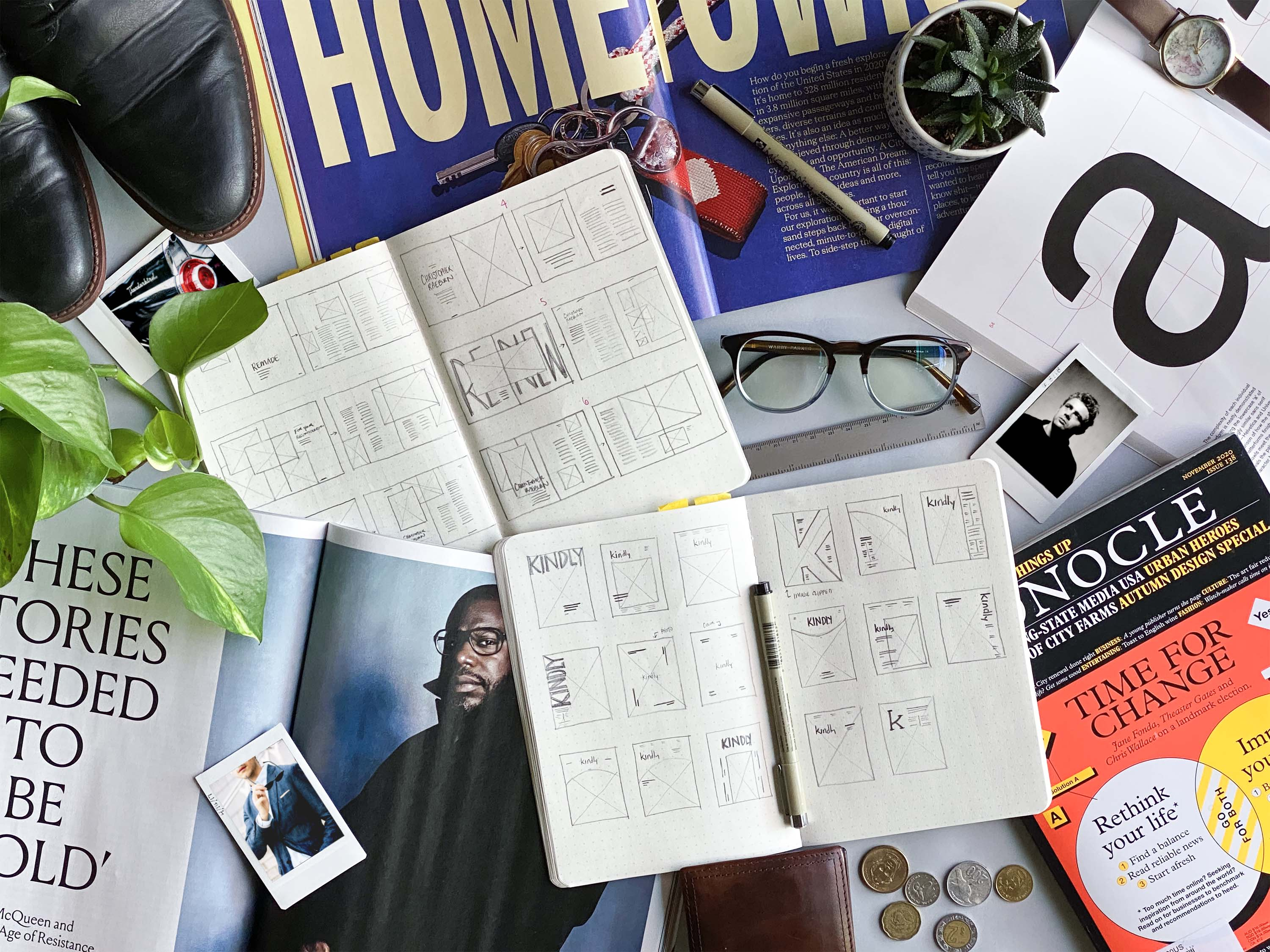 A desk covered in sketchbooks, magazines, and inspiration photos, showing the design process Kindly Magazine.