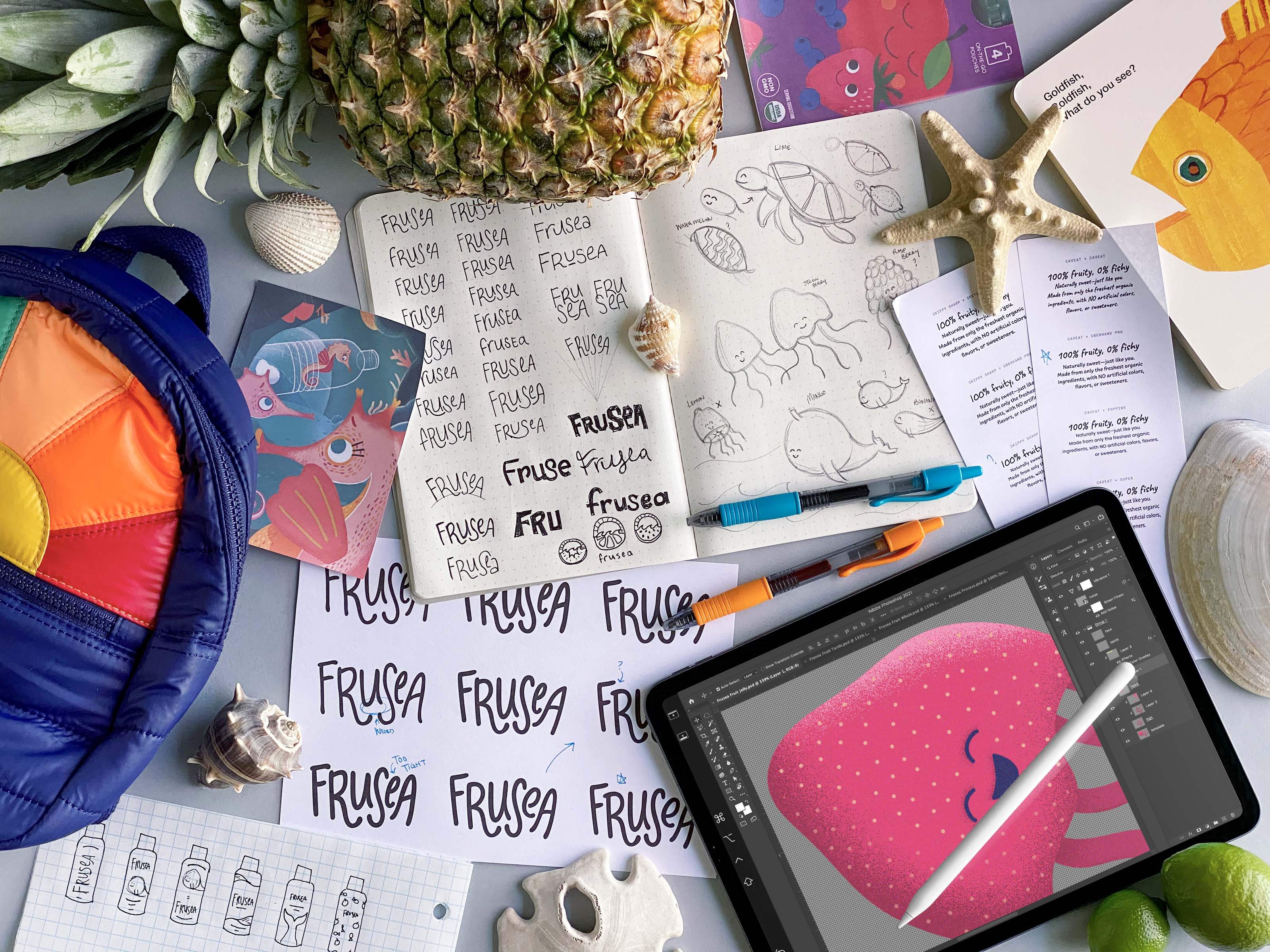 A desk covered in sketchbooks, fruits, and inspiration photos, showing the design process for the project.