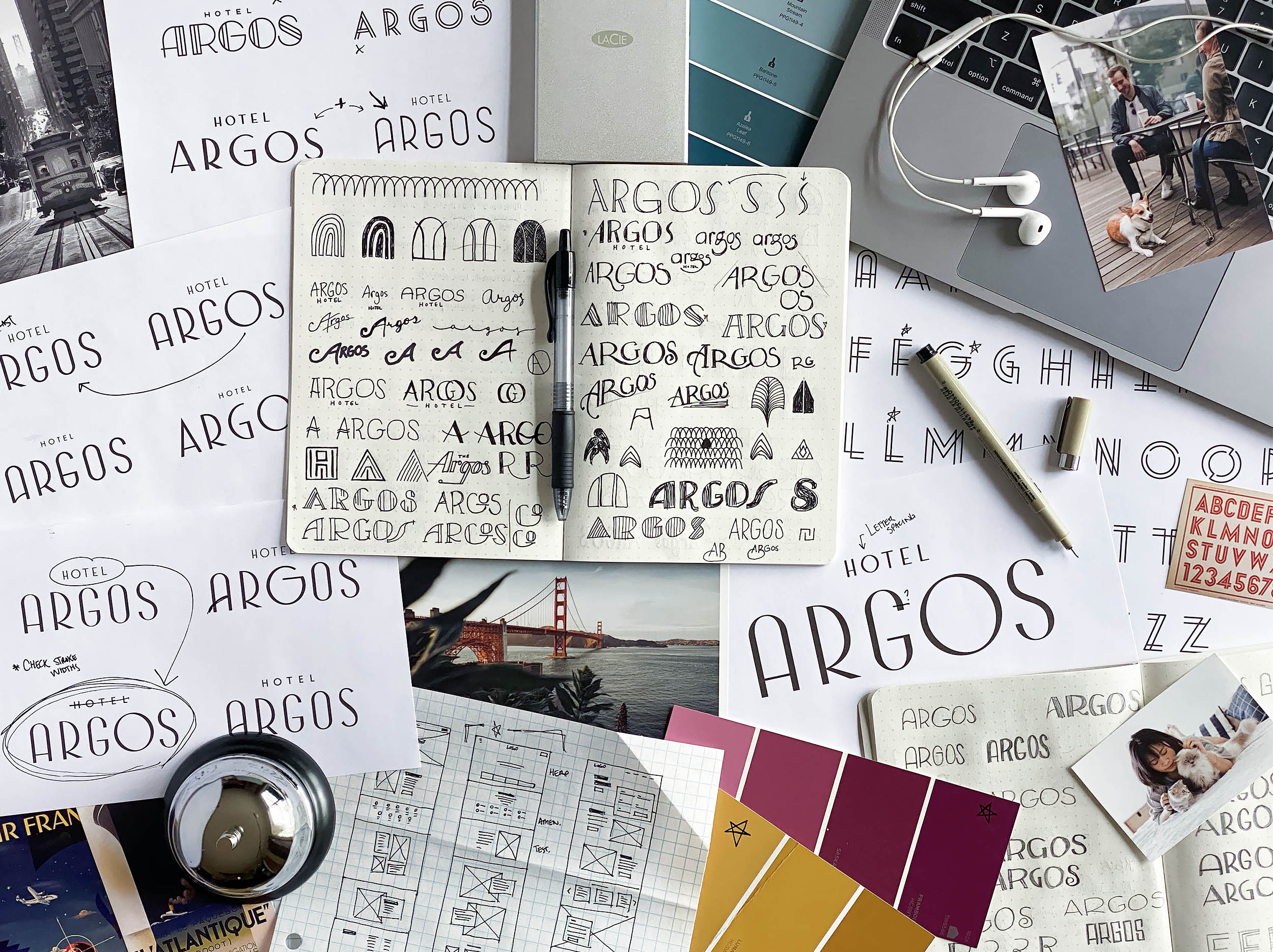 A desk covered in sketchbooks and inspiration photos, showing the design process for Hotel Argos.