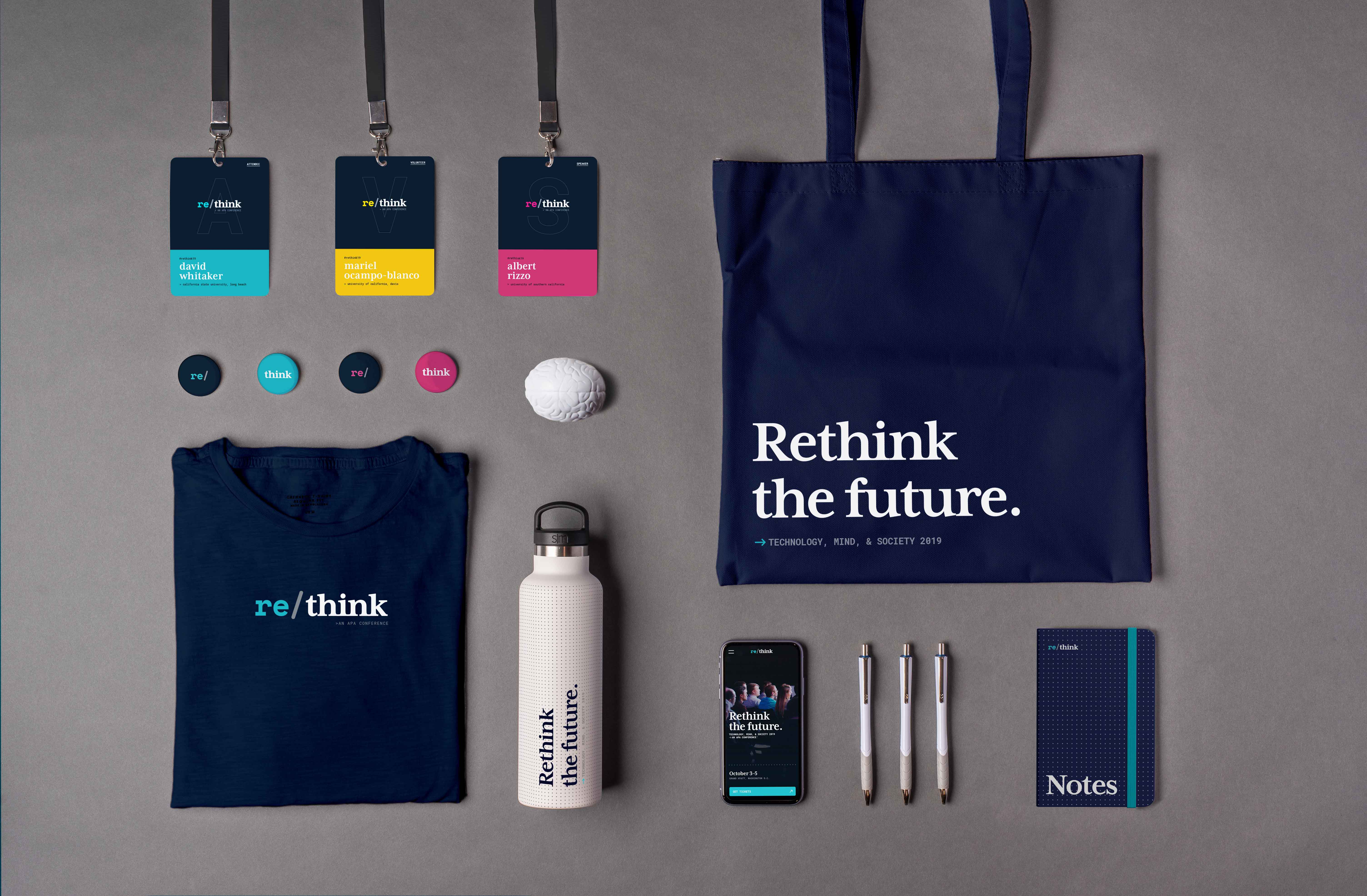 An overview shot of the conference collateral, showing  name badges, buttons, t-shirt, water bottle, tote bag, and notebook