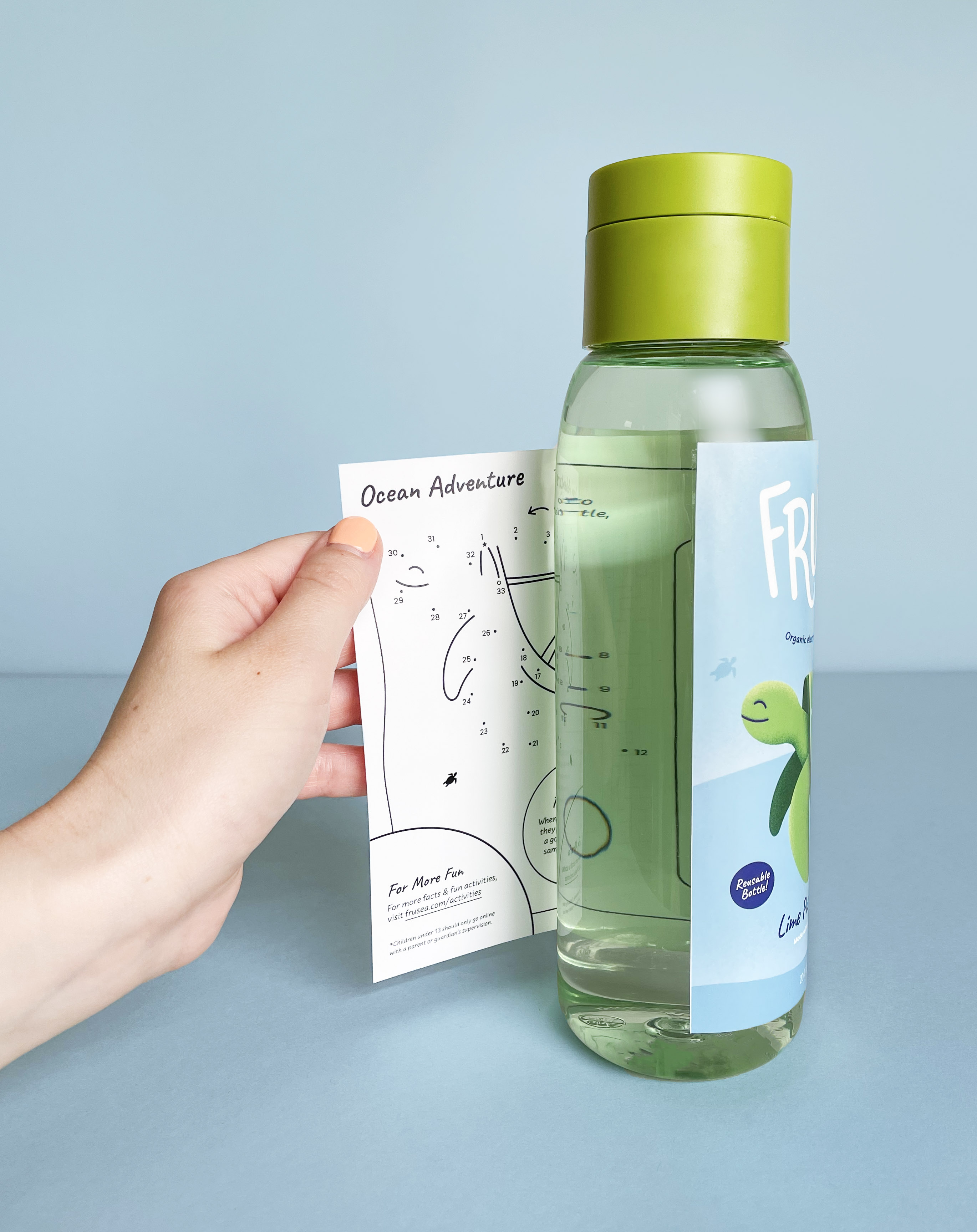 A hand peeling away the bottle label to reveal the activity sheet on the reverse