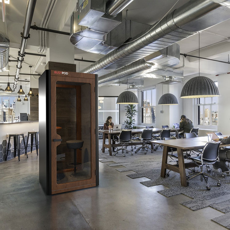 BUSYPOD Phone Booth, Black sides, Walnut frame in an open office