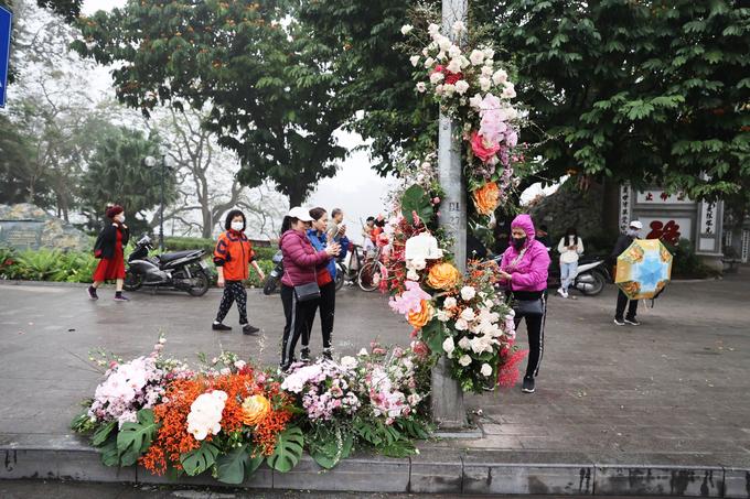 Sáng 8/3, người dân quanh khu vực hồ Hoàn Kiếm bất ngờ khi những cột đèn bỗng biến thành cột hoa tươi rực rỡ sắc màu. Những khóm hoa được trang trí tỉ mỉ, uốn lượn quanh thân cột, tạo thành điểm check-in độc đáo trong ngày Quốc tế Phụ nữ. Ảnh: Ngọc Thành.