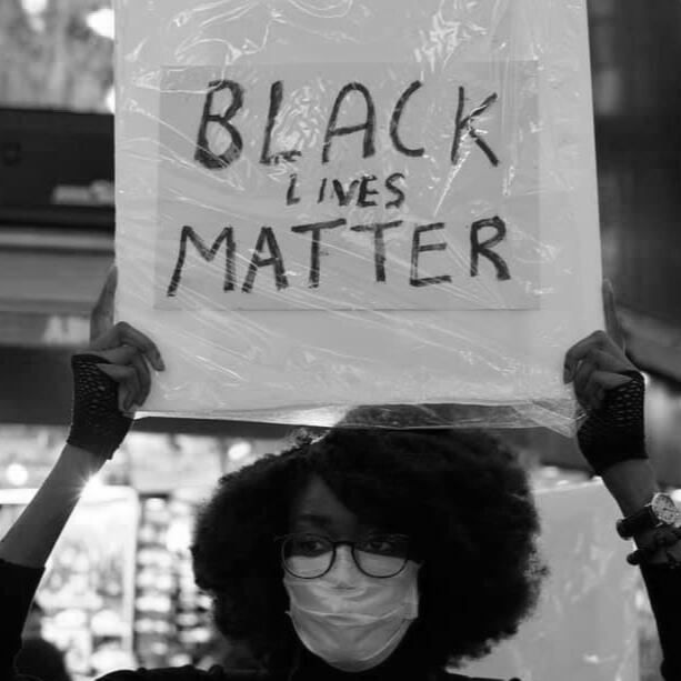 """Black woman holding a sign that says """"Black Lives Matter"""""""