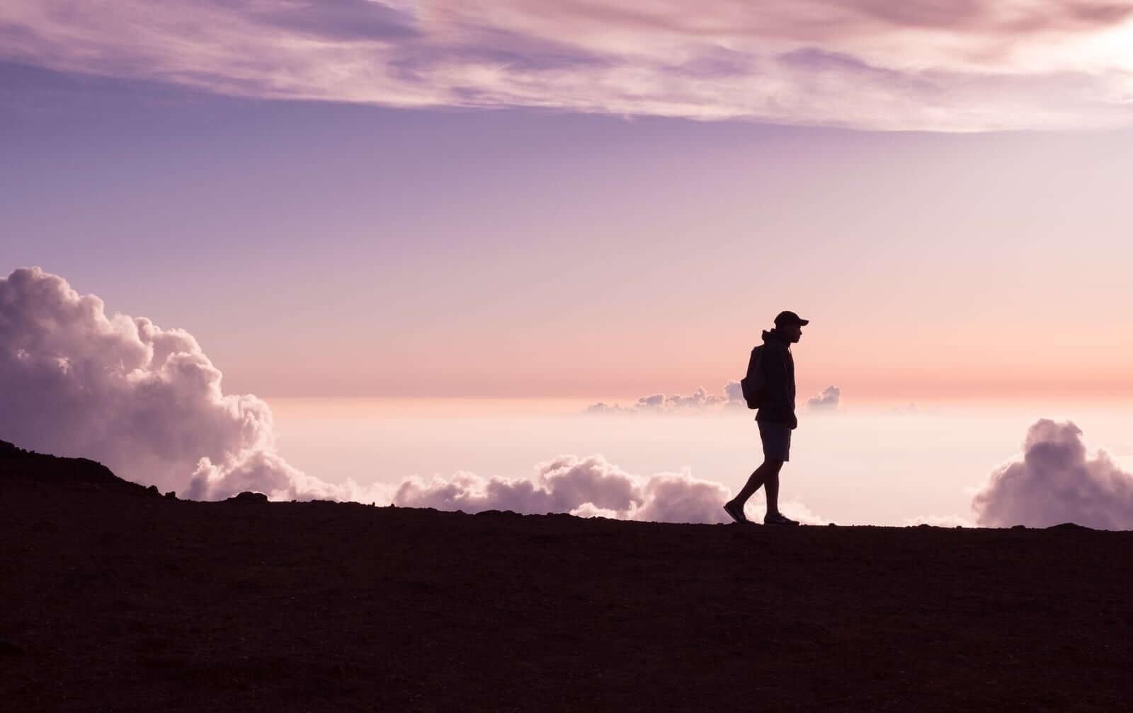 Mężczyzna spacerujący na tle zachodu słońca.