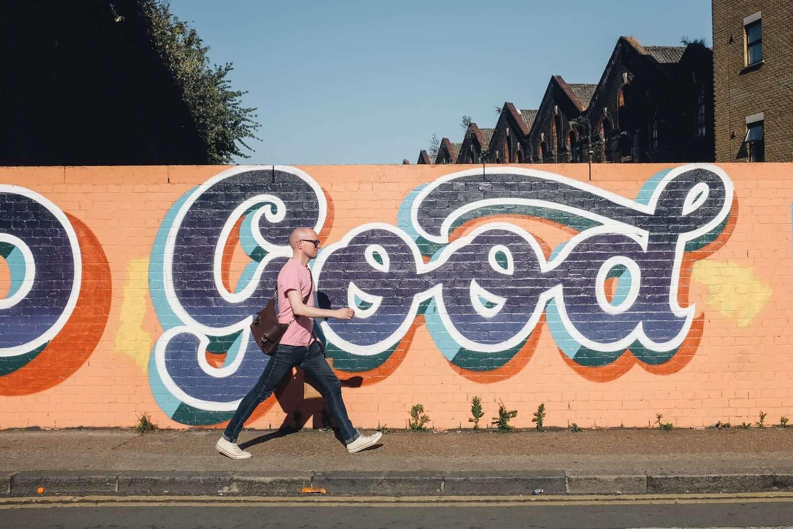 Mężczyzna idący po chodniku na tle grafitti.