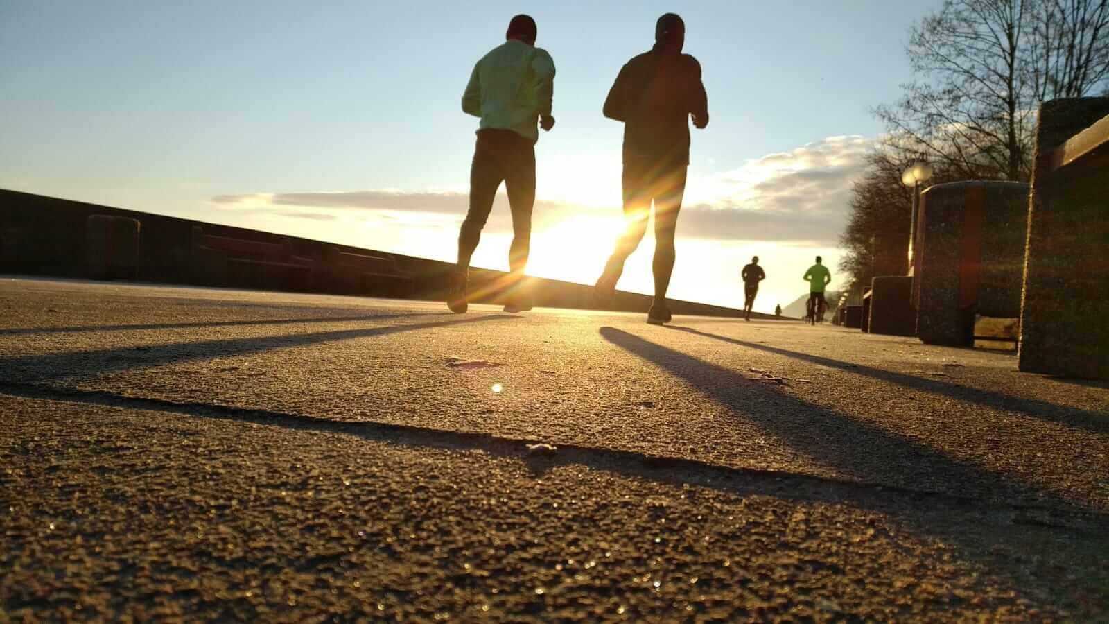 Dwóch mężczyzn biegnie o zachodzie słońca.