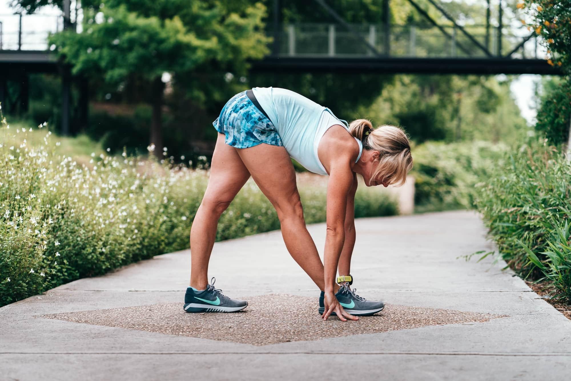 Kobieta rozciągająca się przed treningiem biegowym w parku.