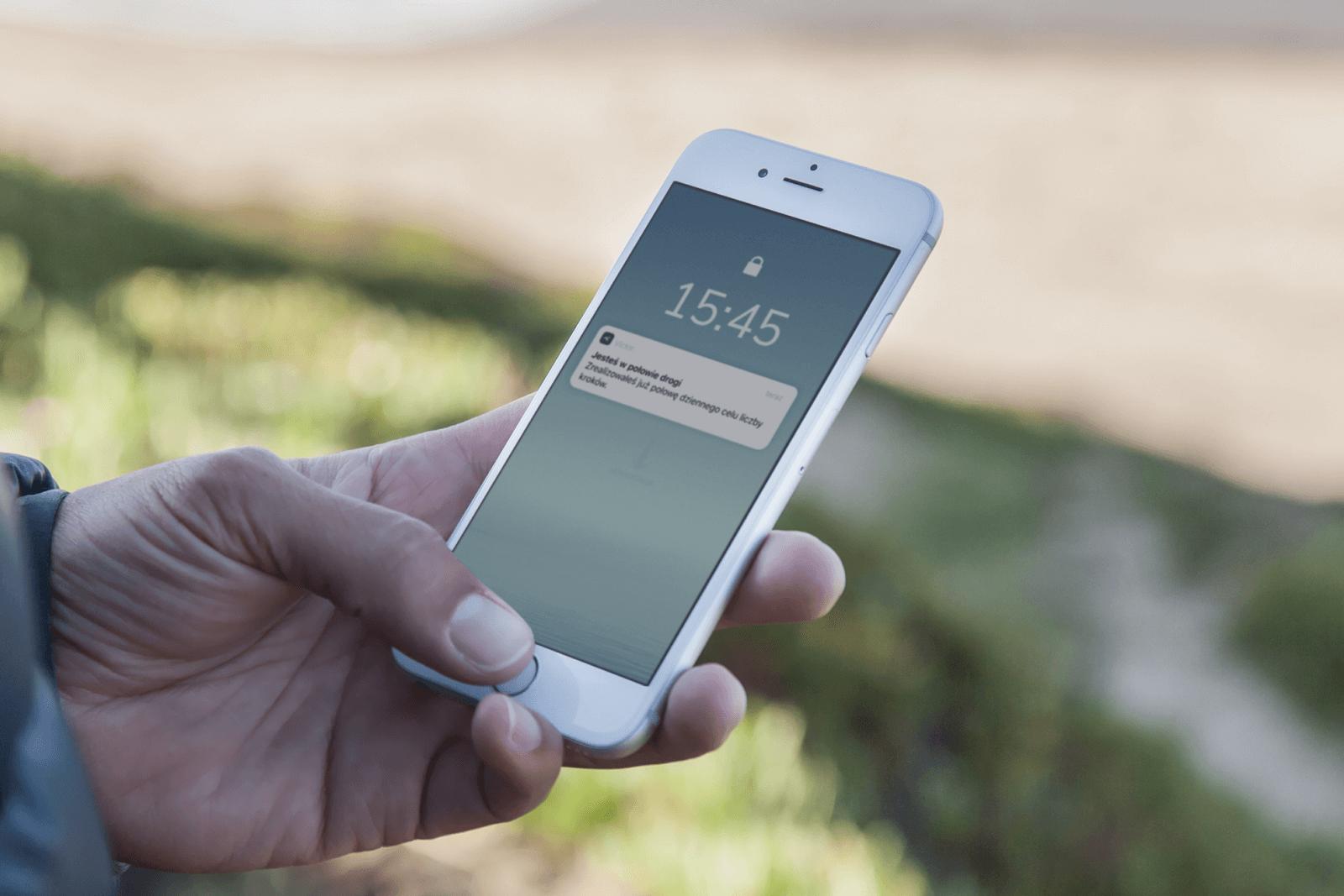 Mężczyzna trzymający telefon, na ekranie telefonu wyświetla się powiadomienie aplikacji Victor.