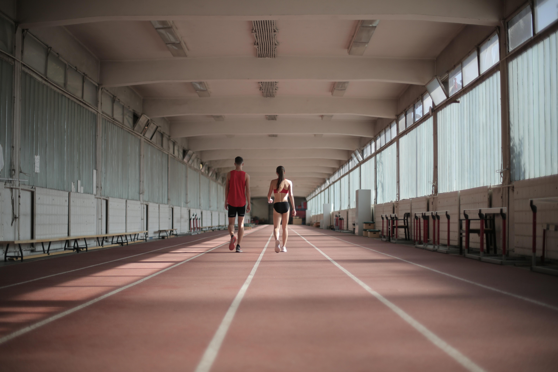 Mężczyzna i kobieta idący po bieżni w zamkniętej hali sportowej.