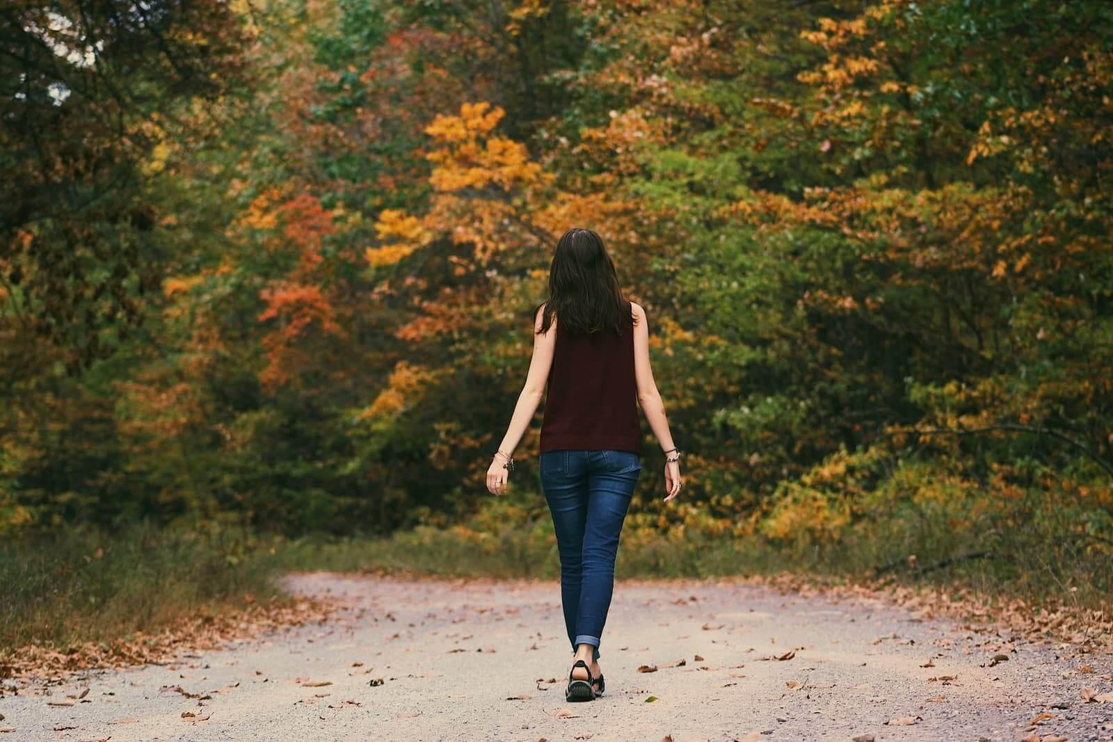 Kobieta idąca po ścieżce wśród drzew
