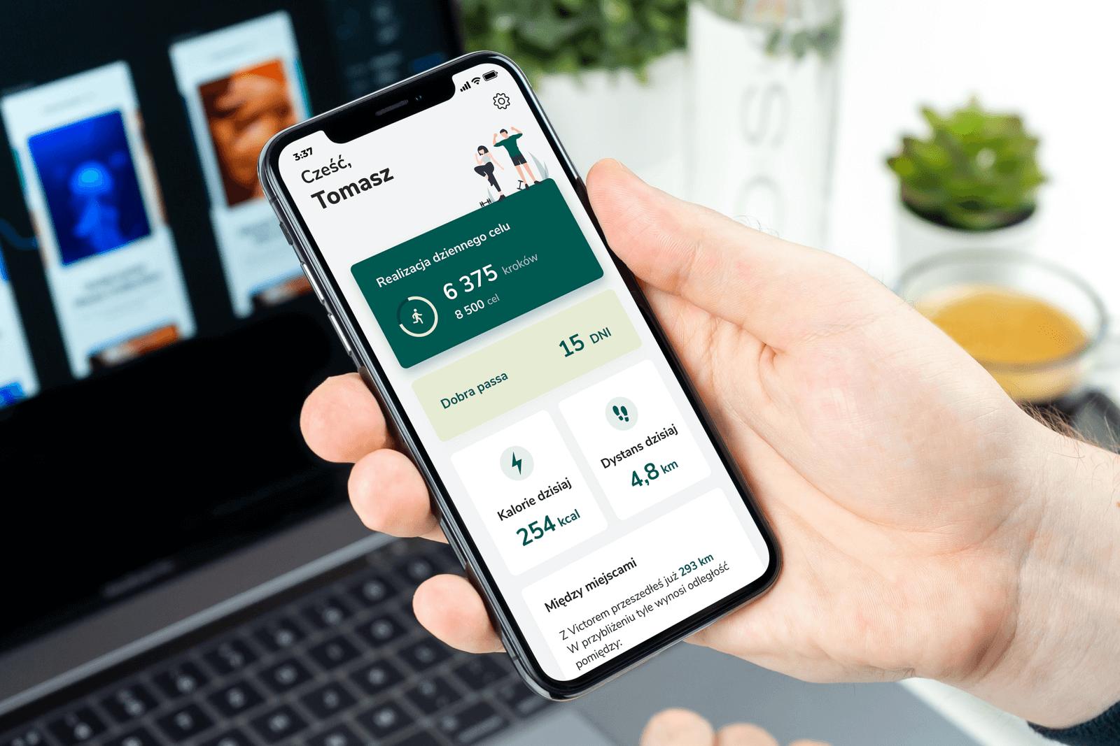 Telefon w dłoni, na ekranie widać aplikację Victor pokazującą ile kroków dziennie przeszedł użytkownik