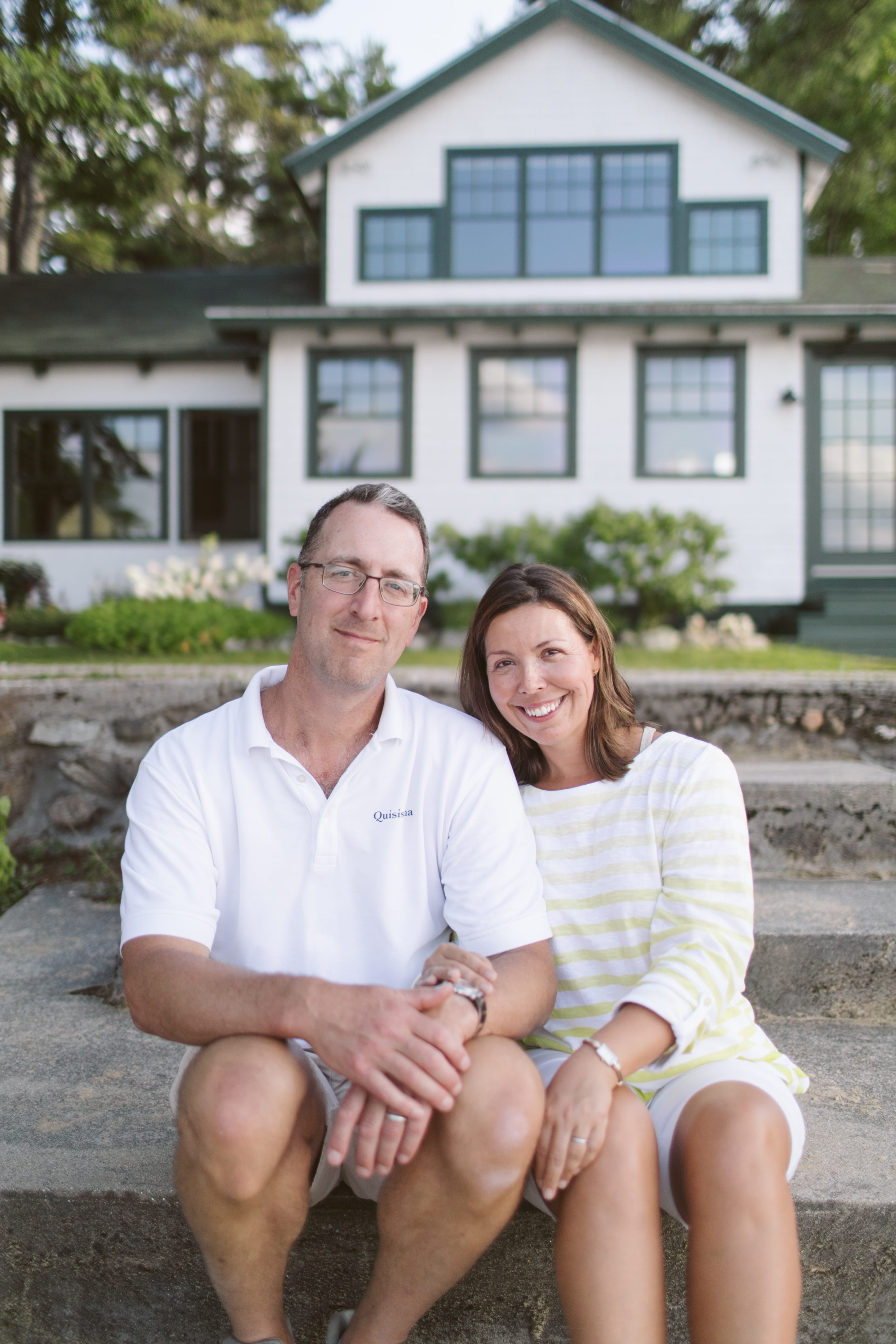 Photo of the two owners of Quisisiana sitting on their front steps