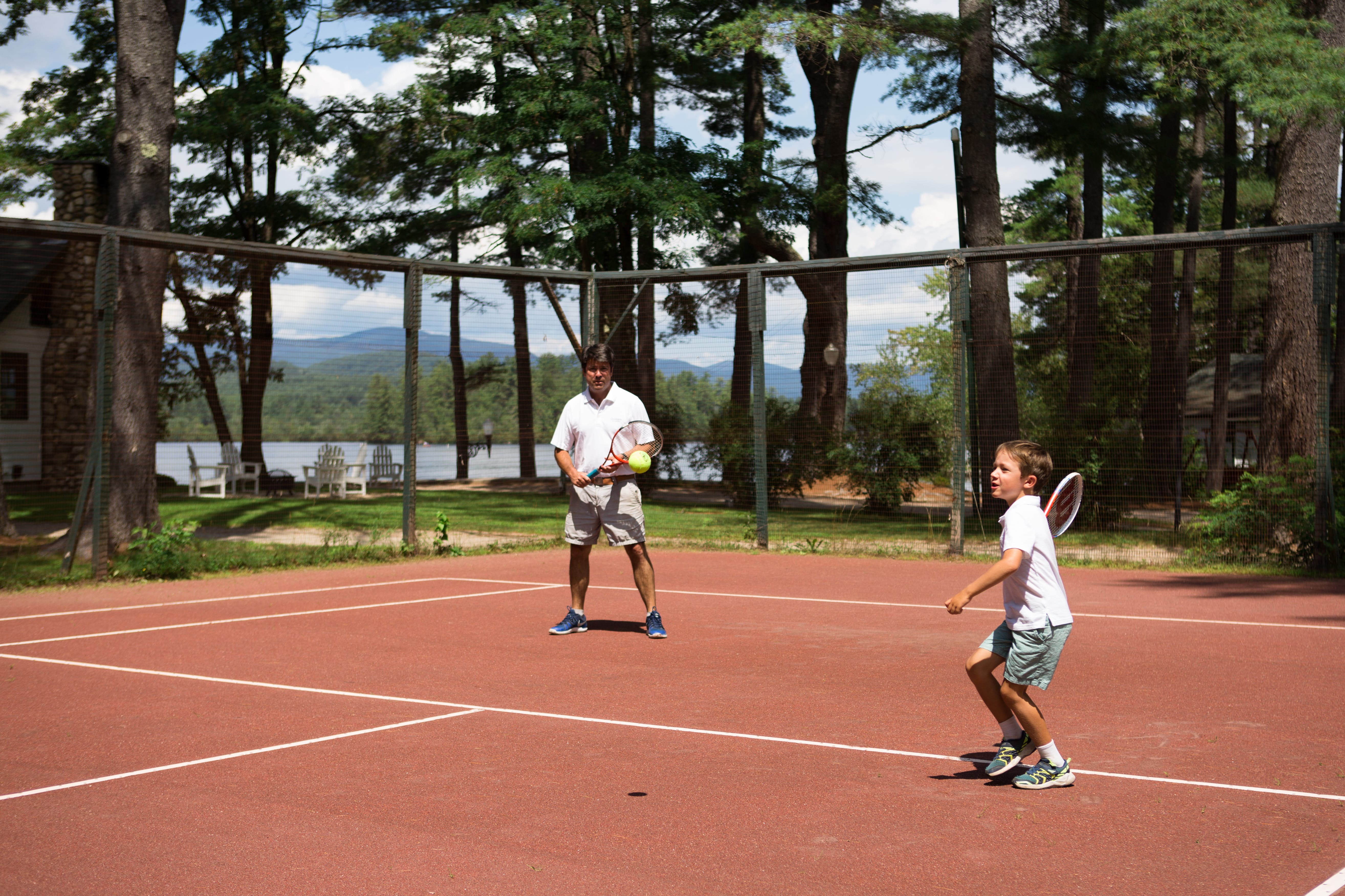 A man and young boy playing tennis