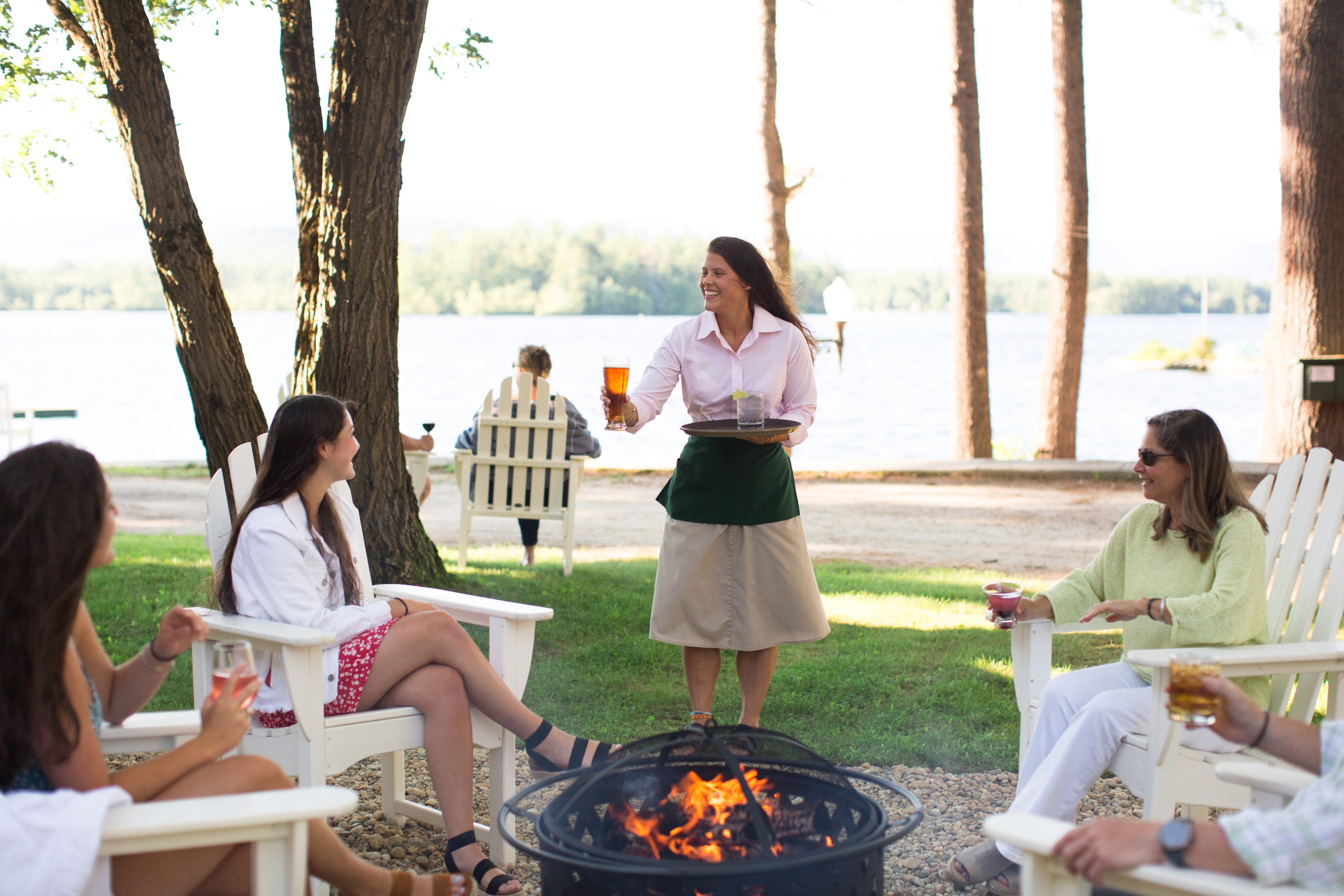 Family sitting around fire pit being served drinks