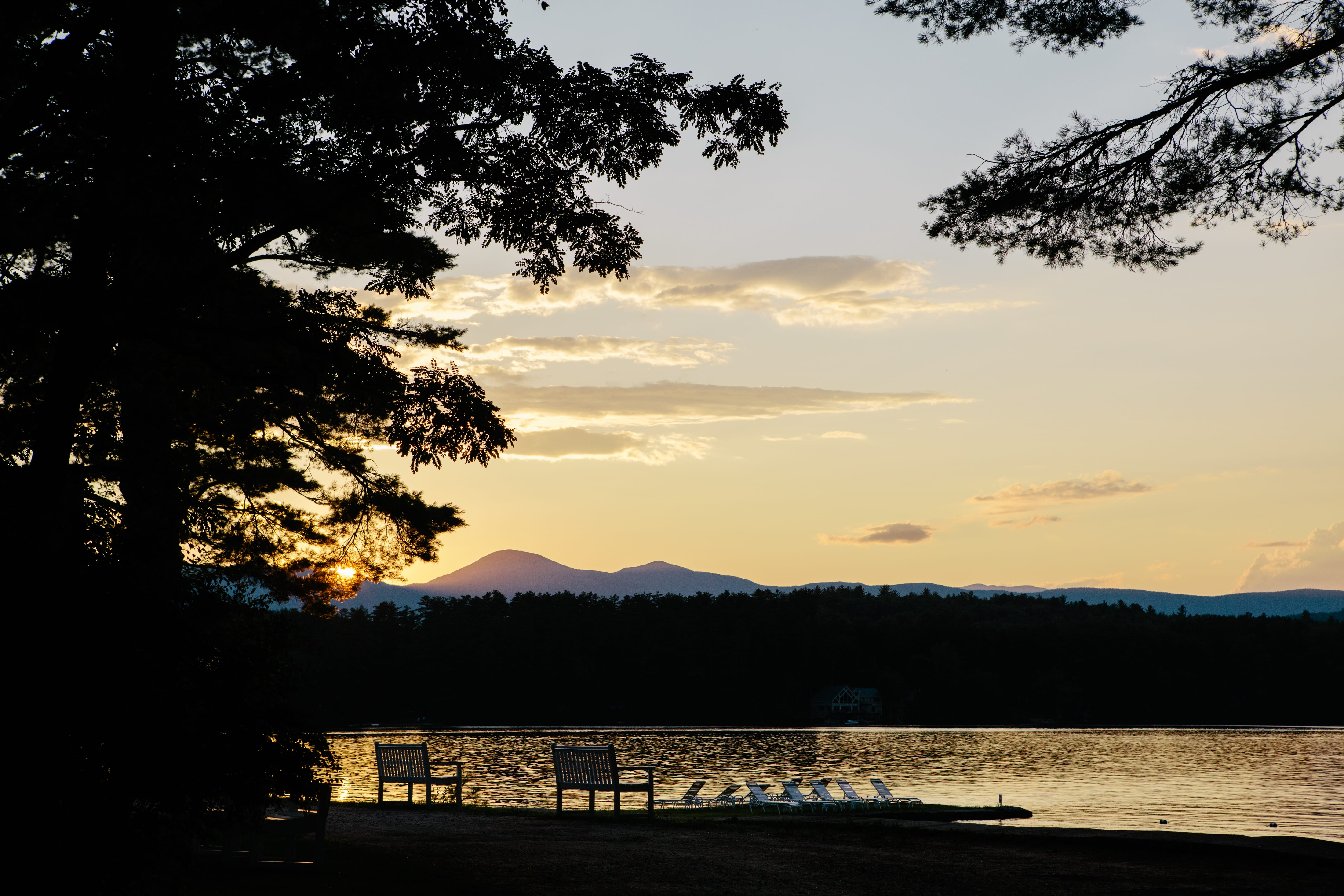 Image of the lake at sunset with two benches and lawn chairs