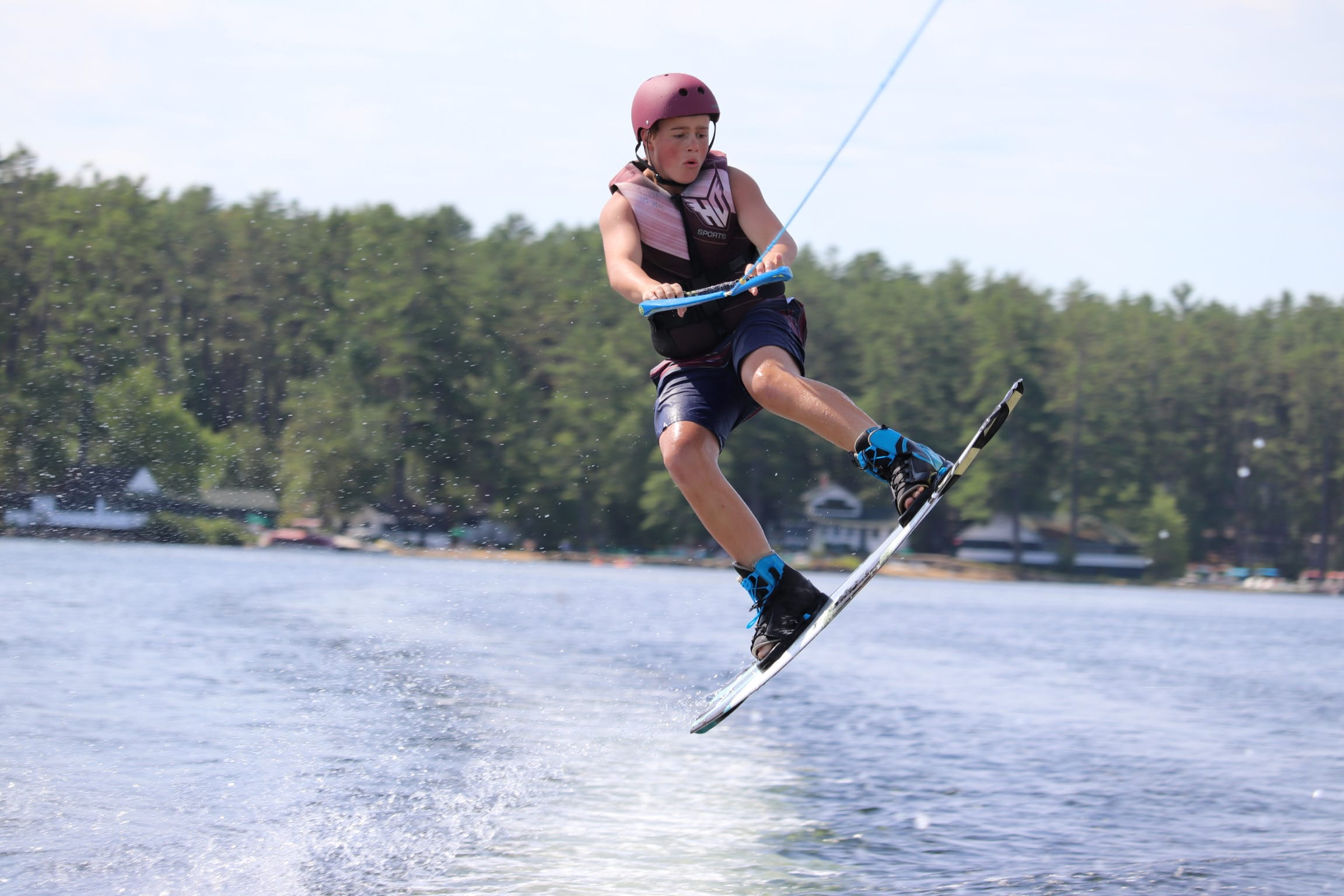 Boy jumping into air with wakeboard