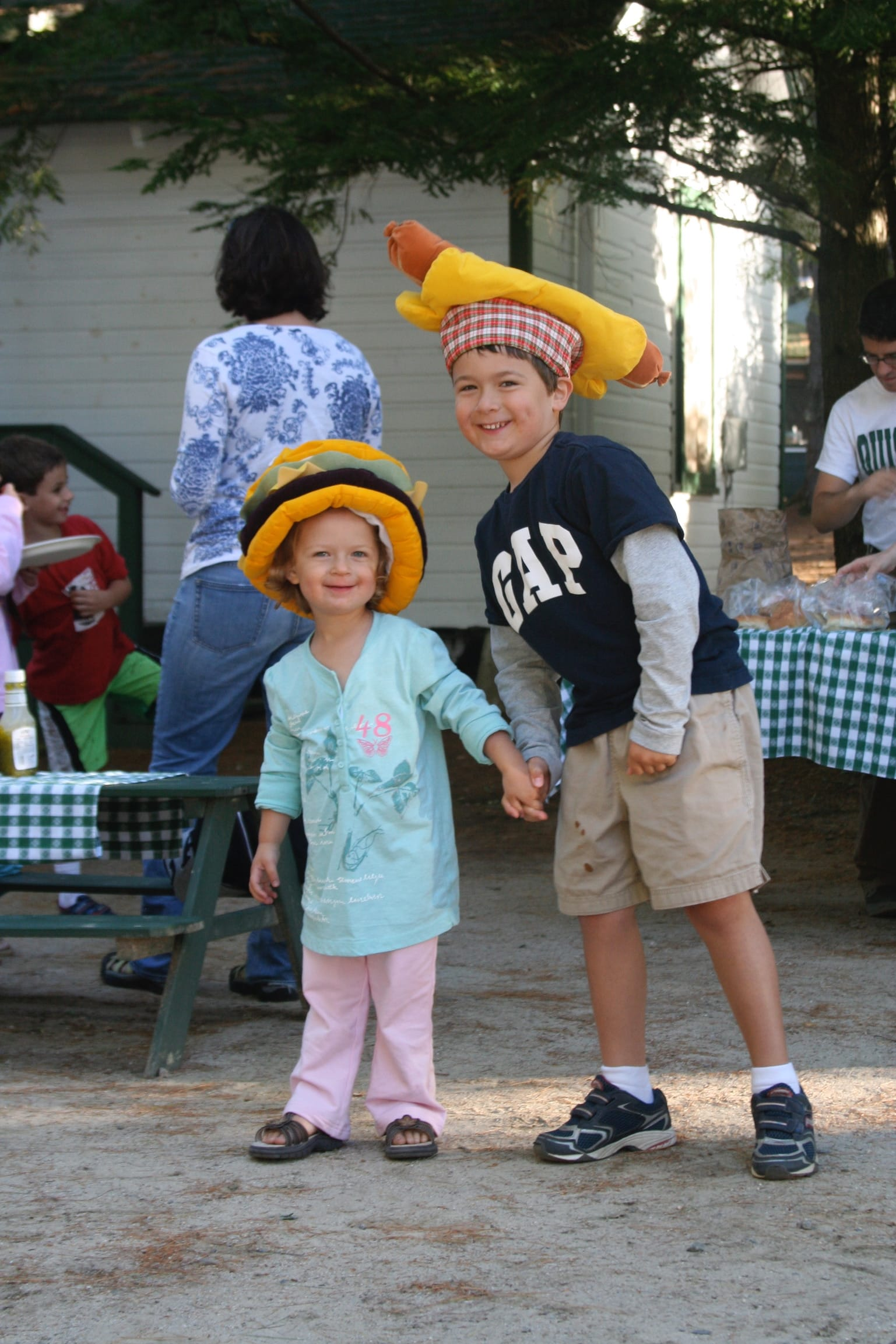 Boy and girl wearing hamburger and hotdog hats