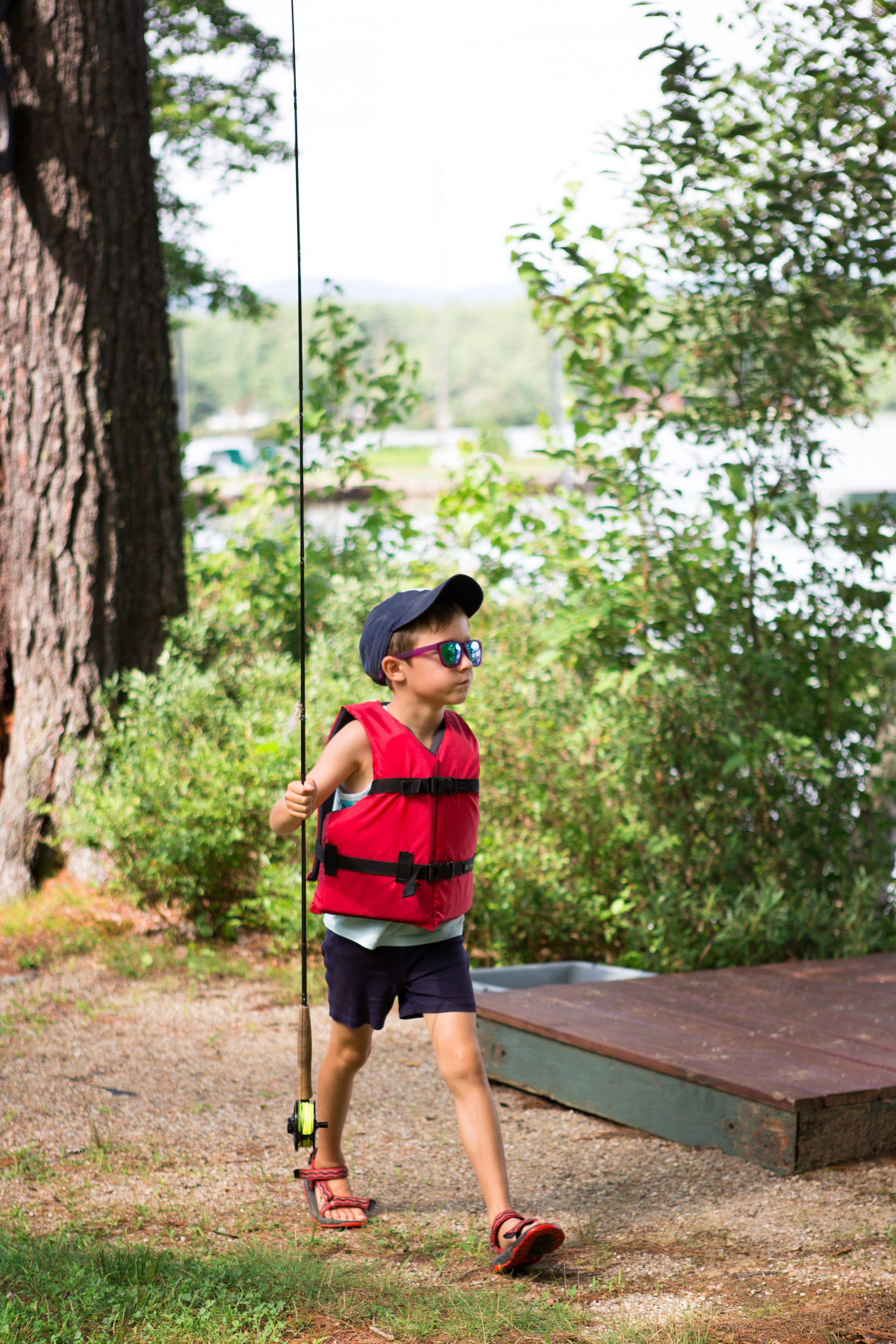 A young boy walking holding a fishing rod