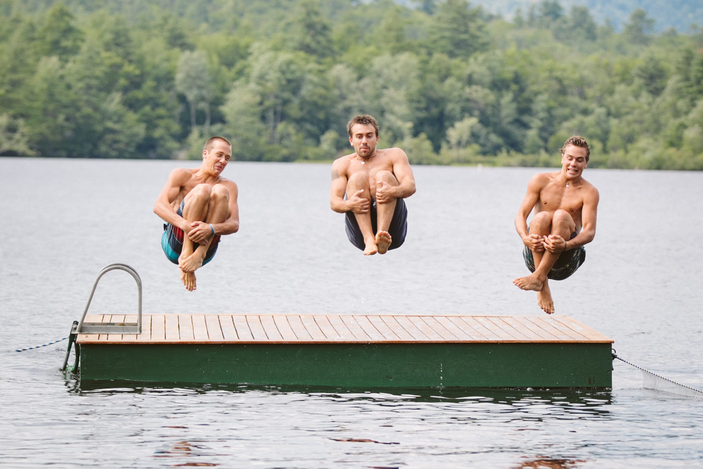 Three men jumping of dock into lake