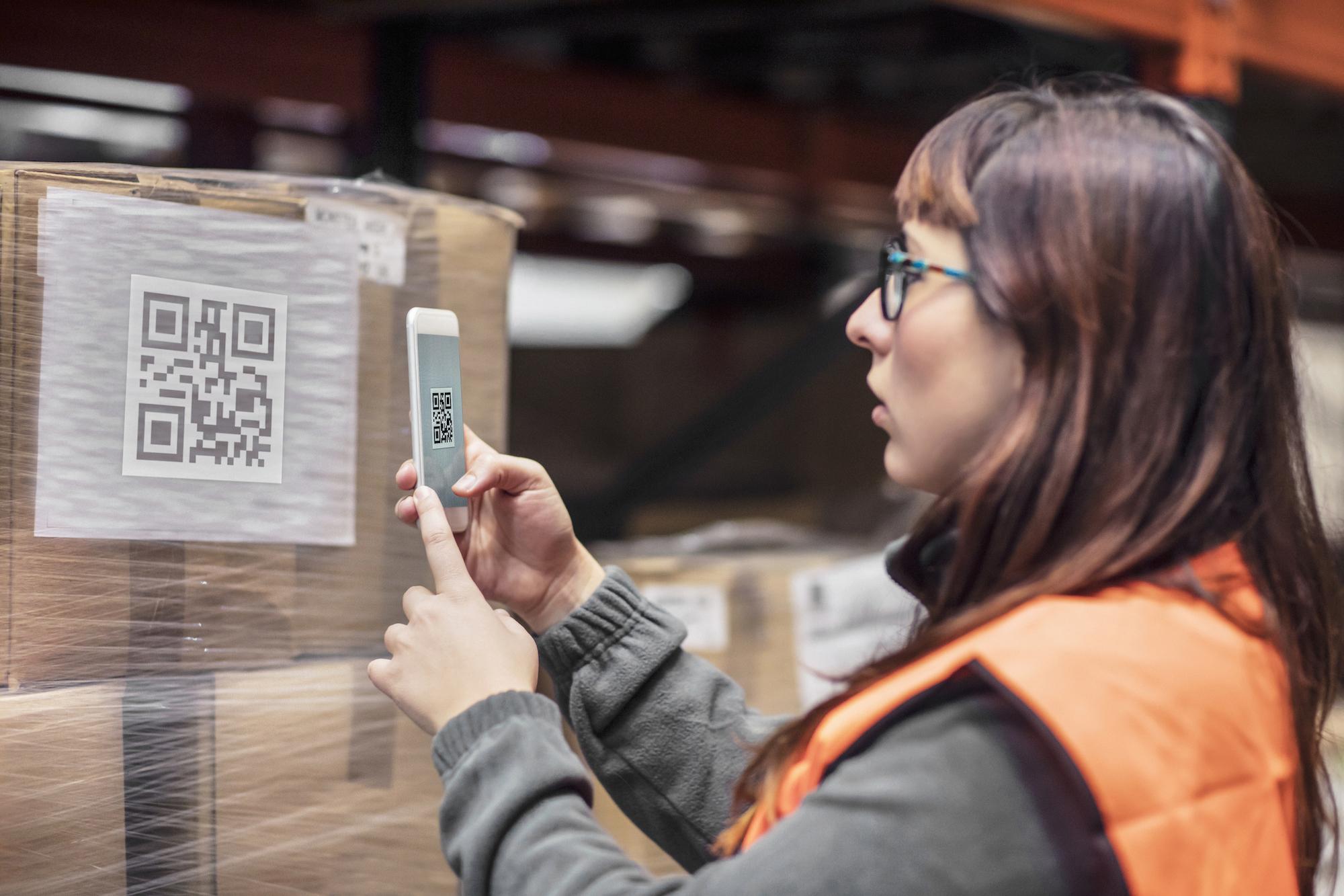 Femme scannant un QR code sur un colis