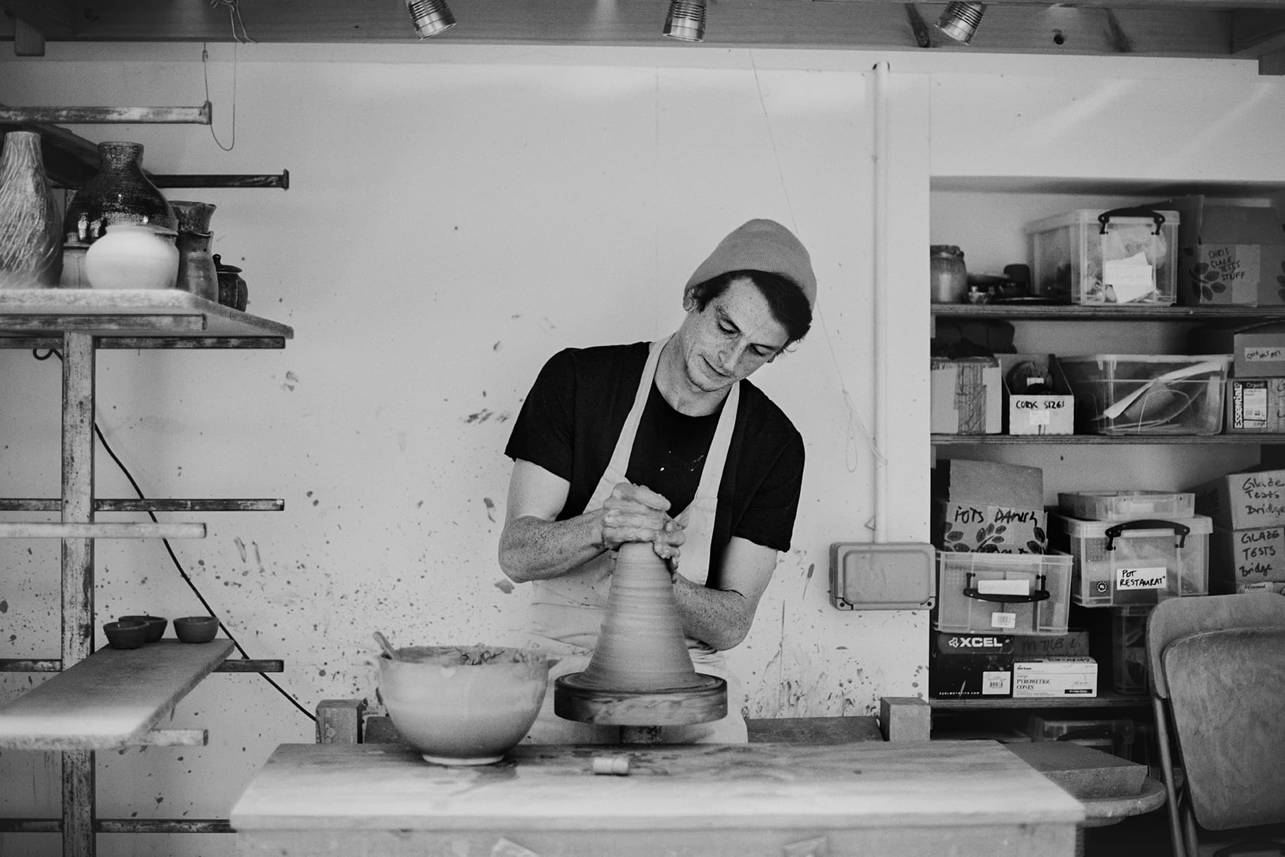 Man making a ceramic pot on a ceramic wheel, black and white image