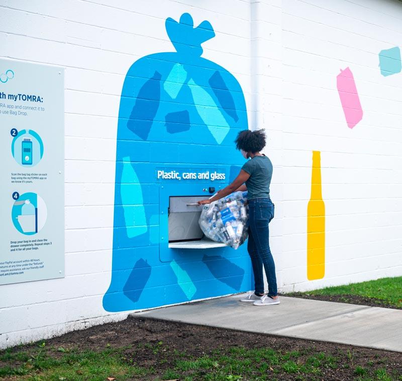 Woman at Clean Loop outdoor recycling bin.