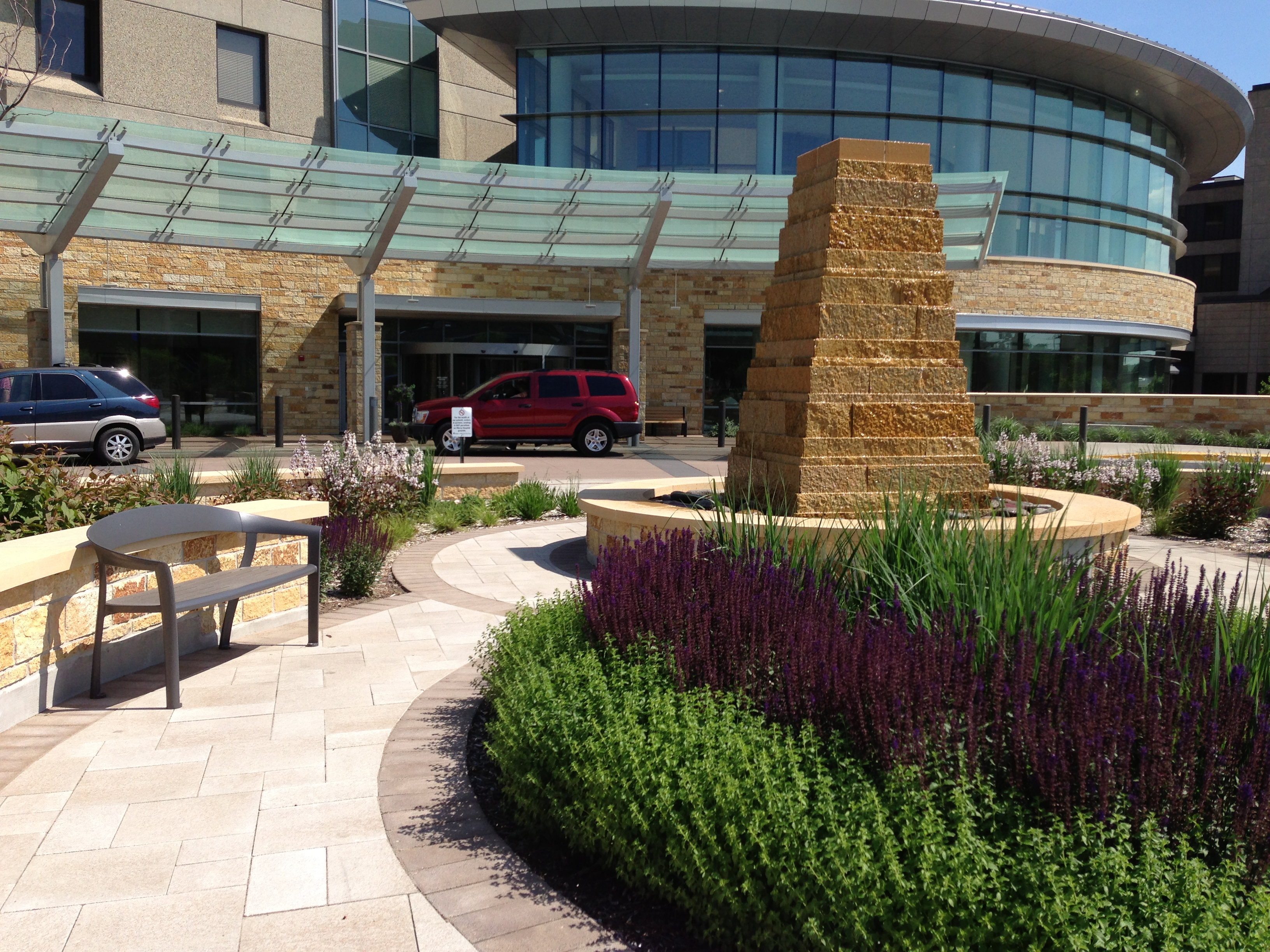 The tower-like water feature is a sentinel at the entry to the hospital and anchors a modest contemplative garden where lush plantings and low limestone seatwalls embrace users and buffer the energy of the parking lots, drive aisles and front door.