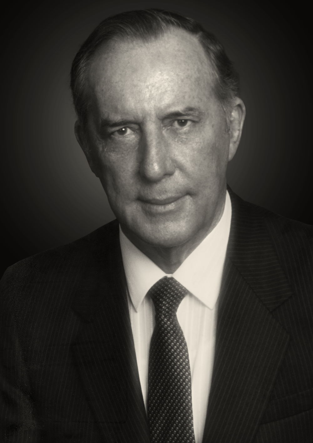 A black and white portrait of Derek Prince wearing a suit and tie.
