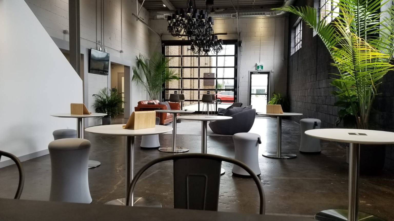 Image of a well lit, open office setting with various types of seating, tables and plants.