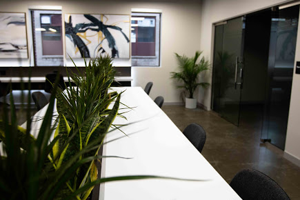 Image of a desk and plant in open office setting.