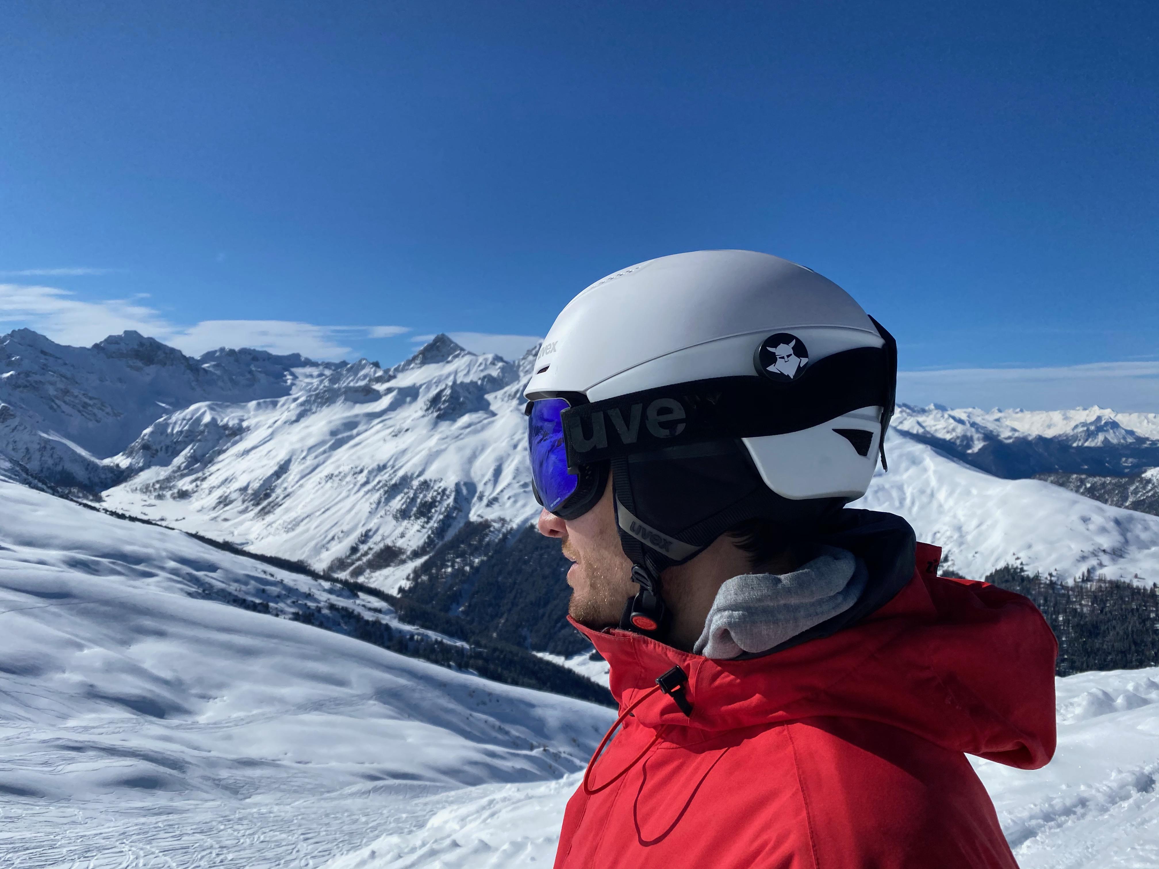 Skifahrer mit Tocsen am Helm in den verschneiten Alpen