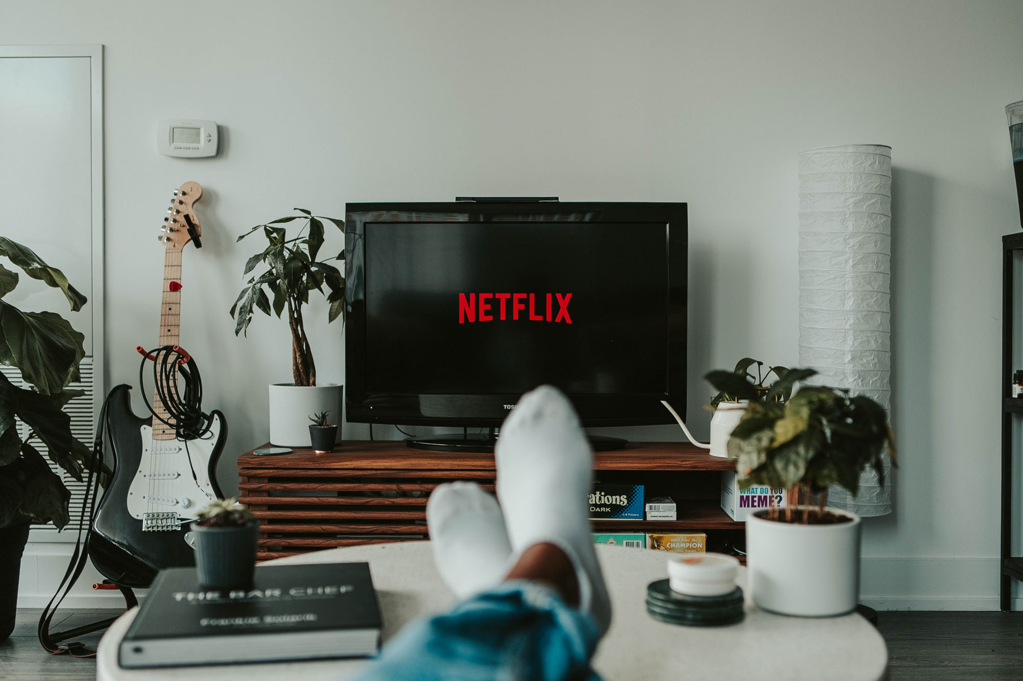 Person watching Netflix on couch as example of negative habit