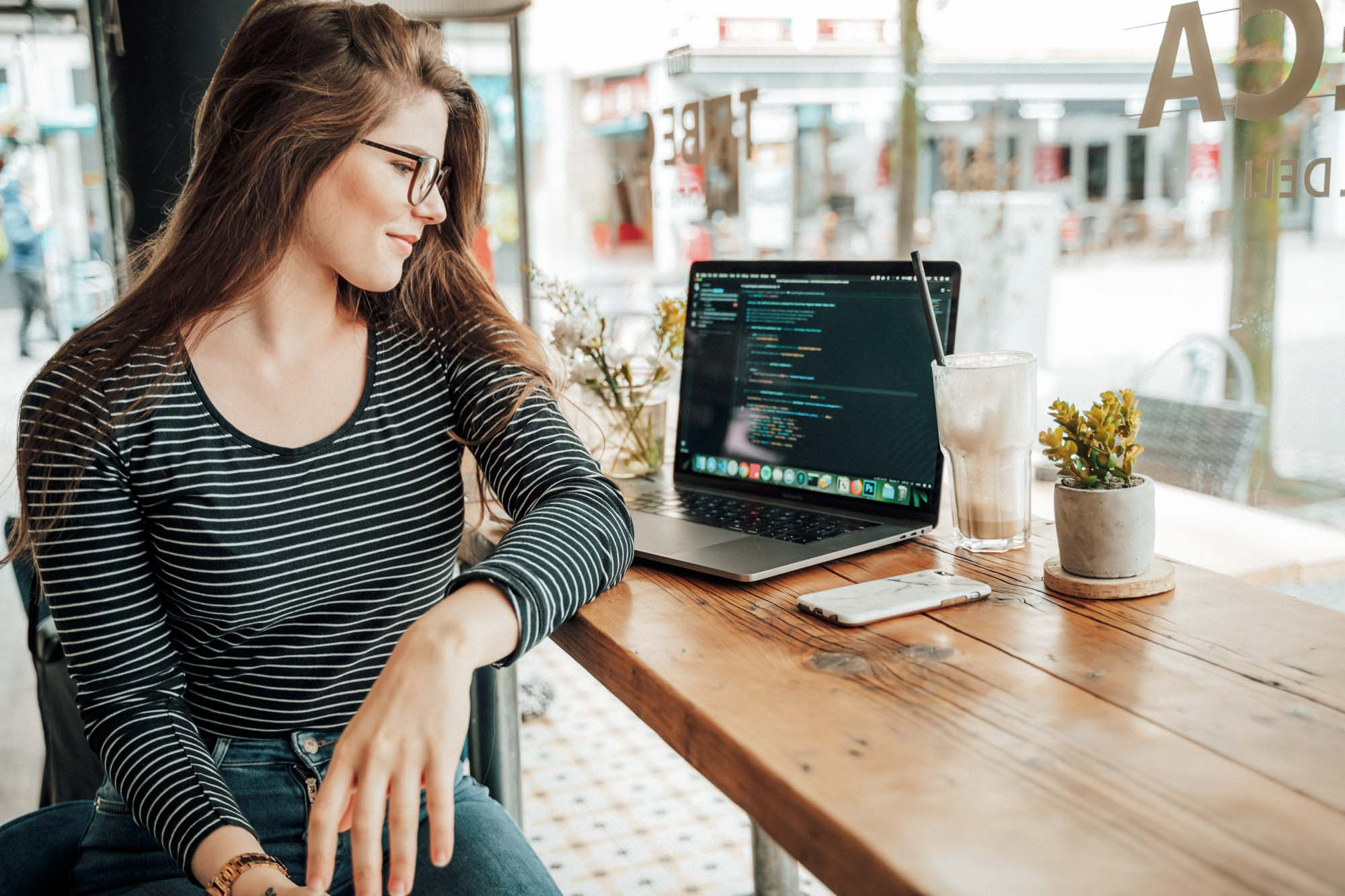 Woman sitting in cafe using laptop for coding