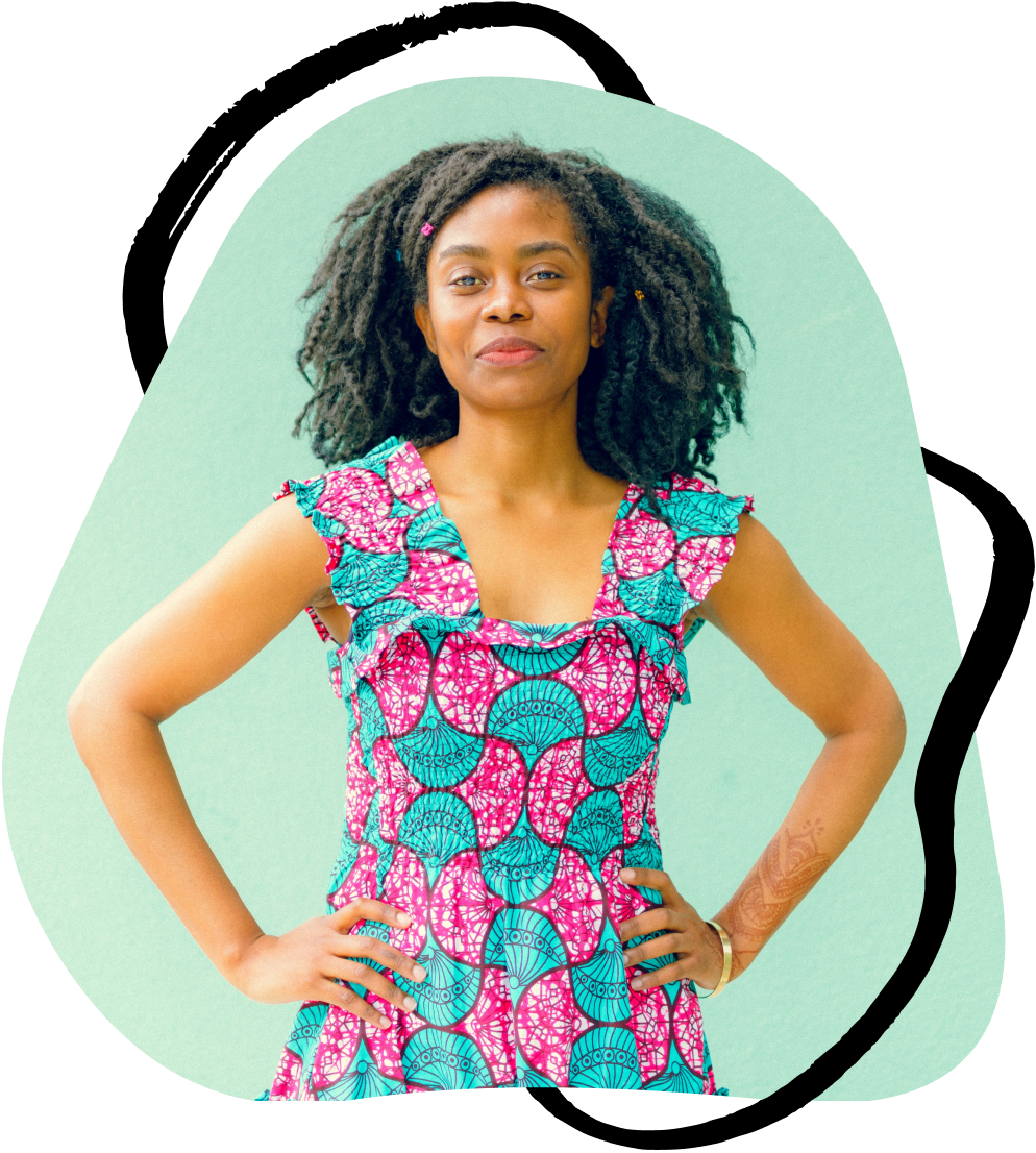 A Black business woman stands with her hands on her hips and looks into the camera powerfully.