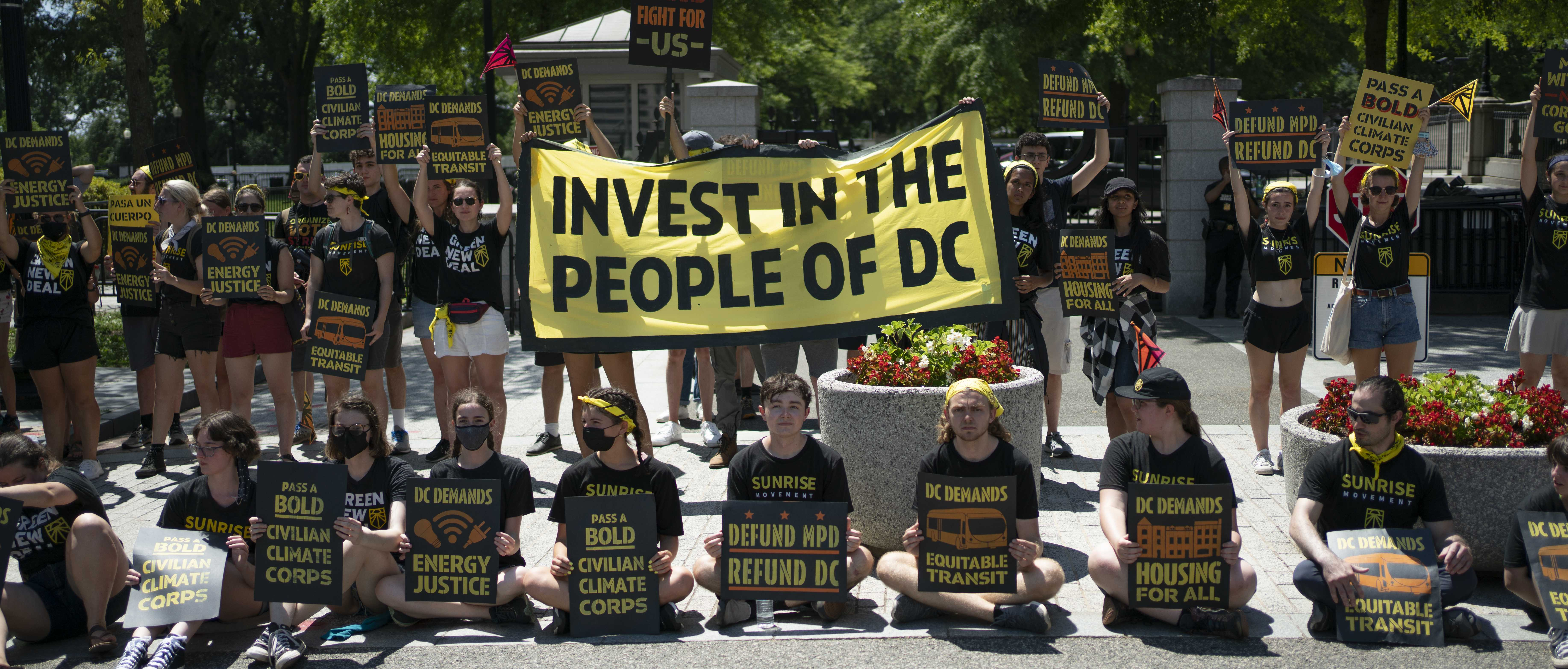 """Sunrise organizers hold signs reading """"Invest in the People of DC"""" and """"Defund MPD Refund DC"""""""