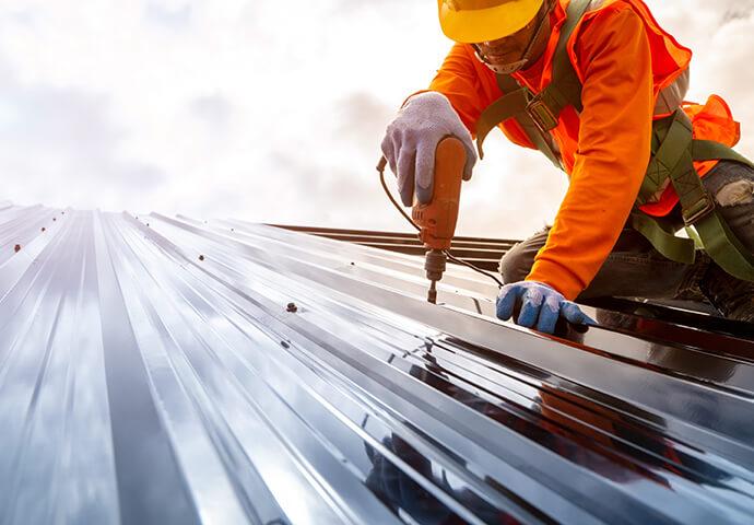 Gegen Absturz gesicherter Arbeiter auf einem Steildach