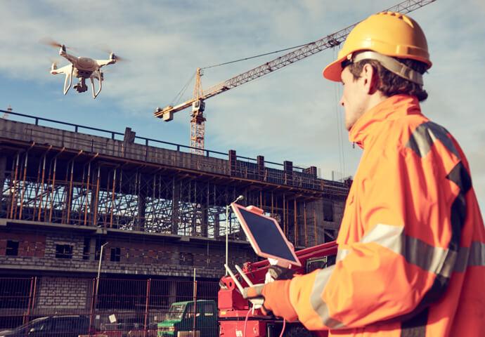 Ein Mann erstellt ein Dachauafmass auf einer Baustelle mit einer Drohne