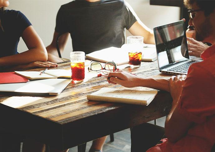 Mehrere Personen sitzen an einem Tisch und führen ein entspanntes Meeting