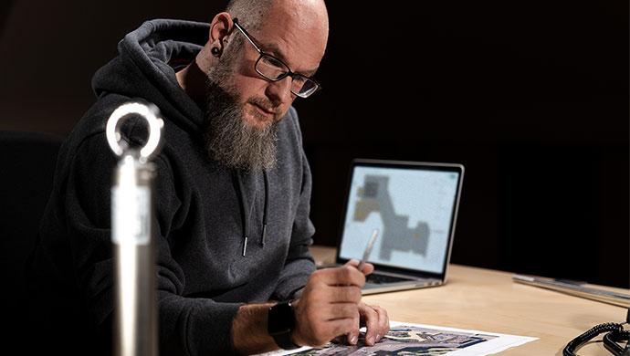 Mitarbeiter betrachtet den Ausdruck einer mit Lock Book Draw erstellten Planungsskizze