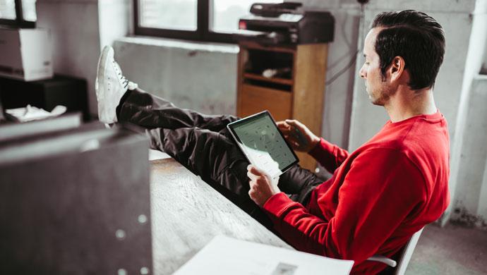 Mitarbeiter bedient Lock Book Docu am Tablet und sitzt lässig am Schreibtisch