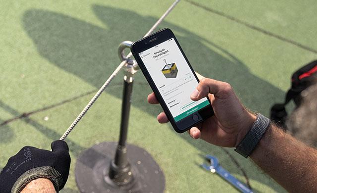 Dacharbeiter*in hält Smartphon in der Hand und dokumentiert Anschlageinrichtung mit der Lock Book Docu App