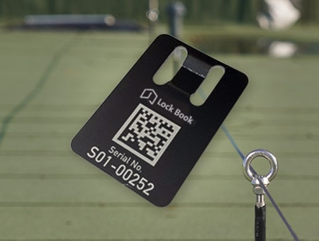 Foto eines Datamatrix-Labels. Im Hintergrund ist eine Dachfläche mit einem Seilsicherungssstem zu sehen.