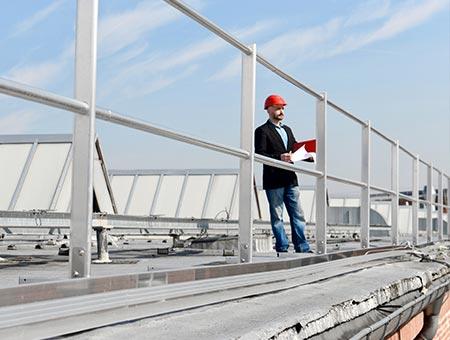 Ingenieur steht auf dem Dach hinter dem Schutzgeländer und hält eine Kladde in der Hand