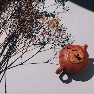 a red clay teapot in white background