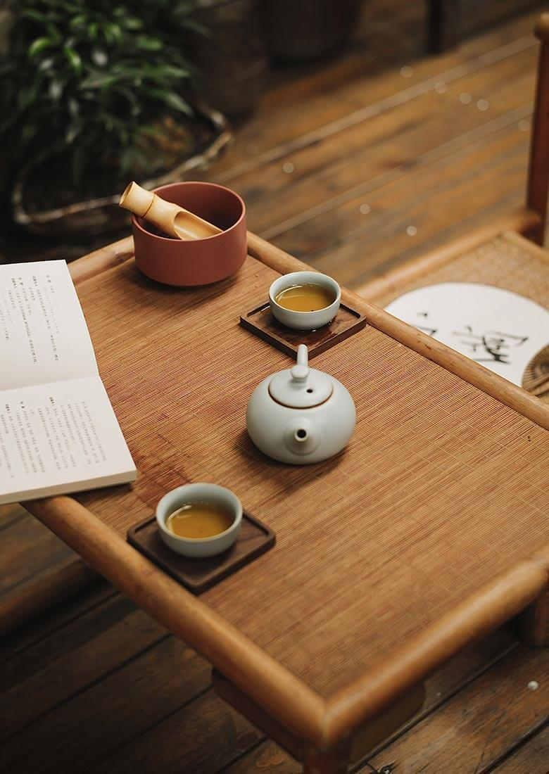 a set of teapot and teacup on a wooden table