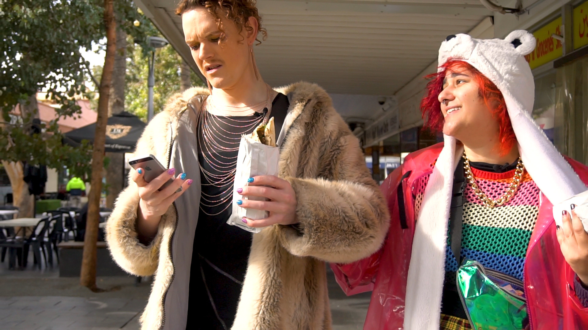 Two nonbinary friends in eccentric clothing look at a phone
